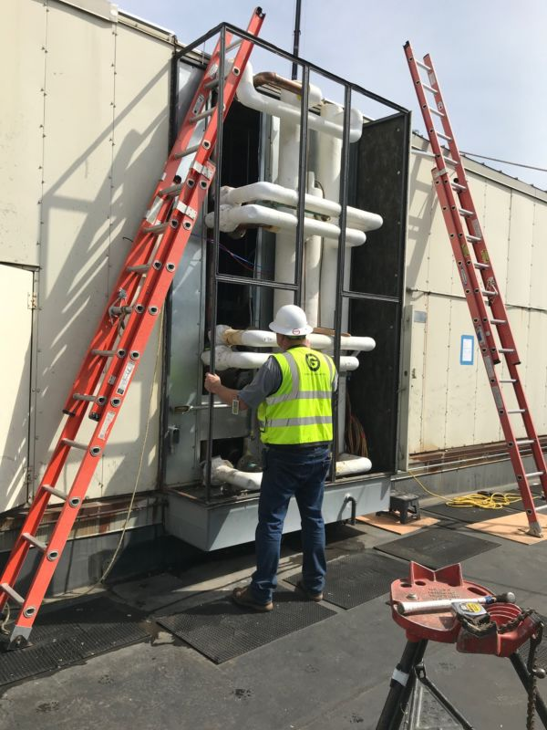 Large cooling coil replacement, engineer in yellow vest